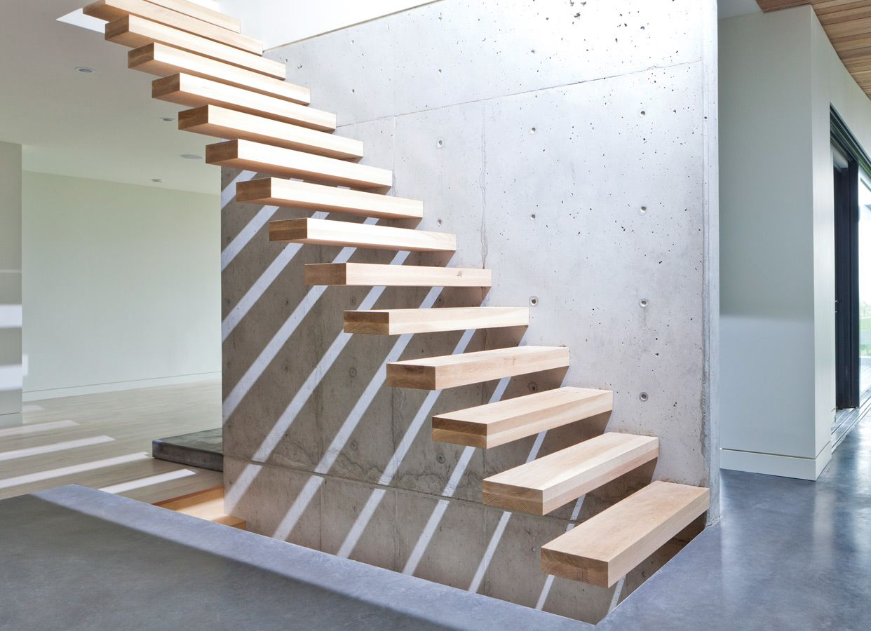 Christian Woo partnered with Asir Studio's Chris Hunter to deliver this home. a cantilevered white oak staircase punctuates a concrete wall, concealing the supporting structure within.
