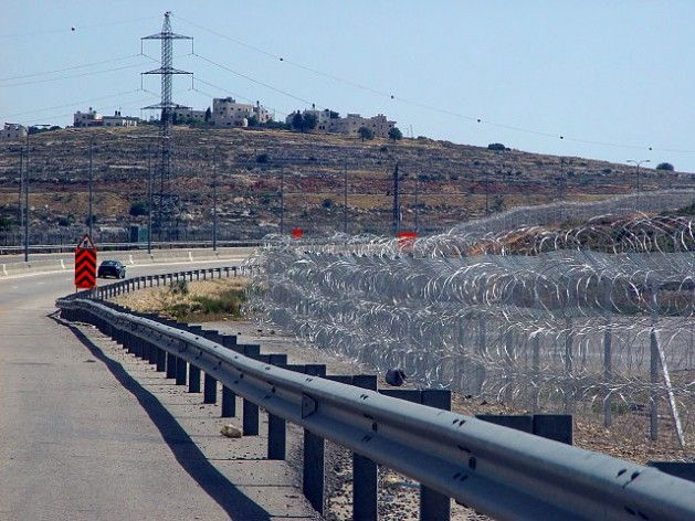 Un tramo de la ruta 443 cerca del cruce de Giv'at Ze'ev. Los alambres de púas forman una sección de la barrera israelí en Cisjordania. Crédi...