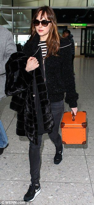 Mixing it up: Walking through Heathrow towards her flight, Dakota showed off her funky bright orange box-shaped suitcase