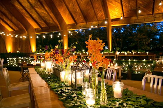 A table runner of leaves and wild flower centerpieces create a gorgeous natural look at this outdoor wedding. Event Design by Mandy Scott Events.