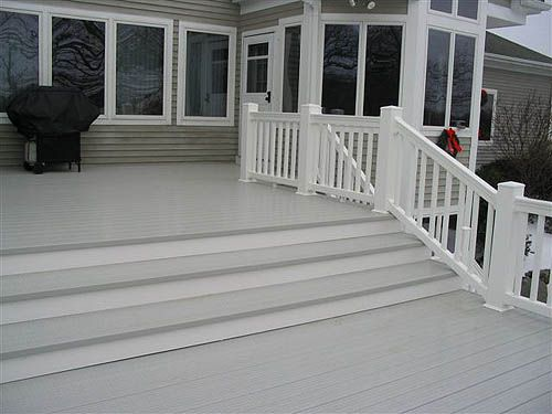 Large gray deck on gray house white railing megadeck for Vinyl decking material