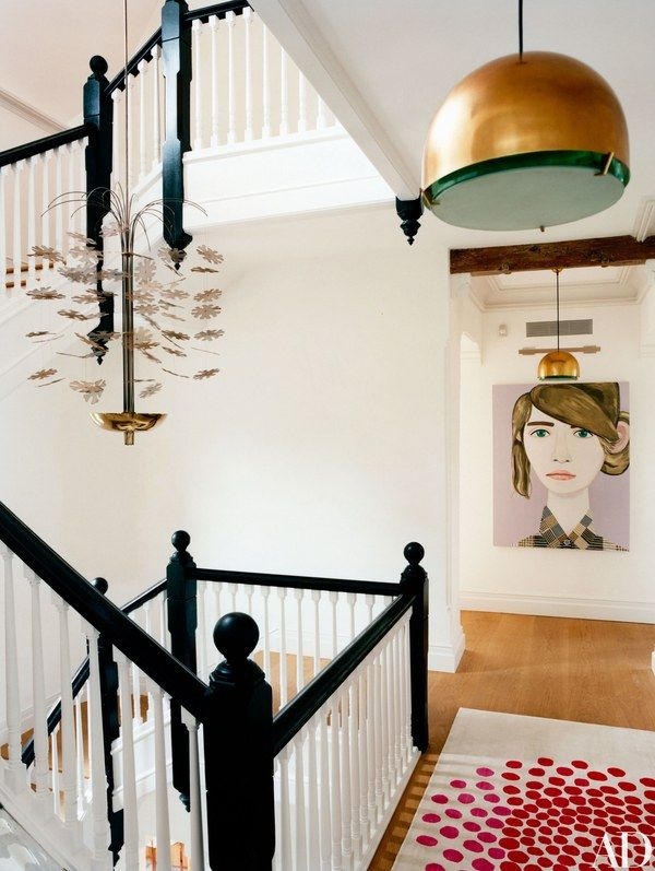 A brass chandelier by Paavo Tynell hangs in the stairwell; the painting in the second-floor hallway is by Brian Calvin.