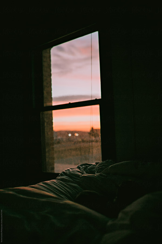Sunrise Or Sunset Through An Apartment Bedroom Window Stocksy
