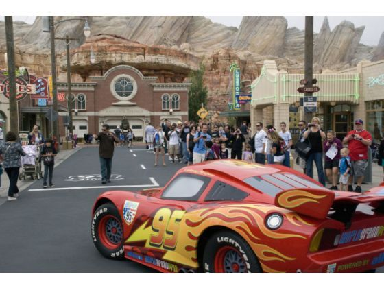 Lightning McQueen, a cartoon character from the Disney/Pixar animated movie Cars, turns the corner in the one intersection of Radiator Springs. The Radiator Springs Courthouse with the Cadillac Mountain Range looming behind it, is in the distance.