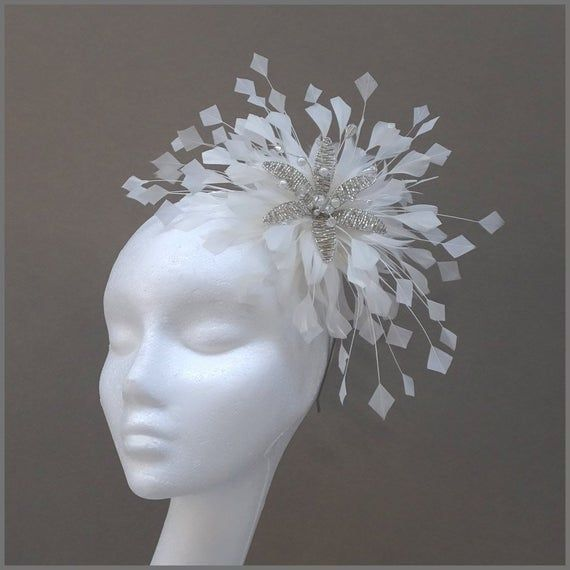 Floral fascinator with large spray of white feathers perfect for weddings, race days or formal occas #fascinatorstyles A pretty fascinator designed with a large spray of white feathers and a crystal flower detail in the centre. Made on a headband.  Designs can be made to order in a range of different colours or styles, see our colour chart: www.jacquivaledesigns.com/colour_chart.html Please contact me if you would #fascinatorstyles