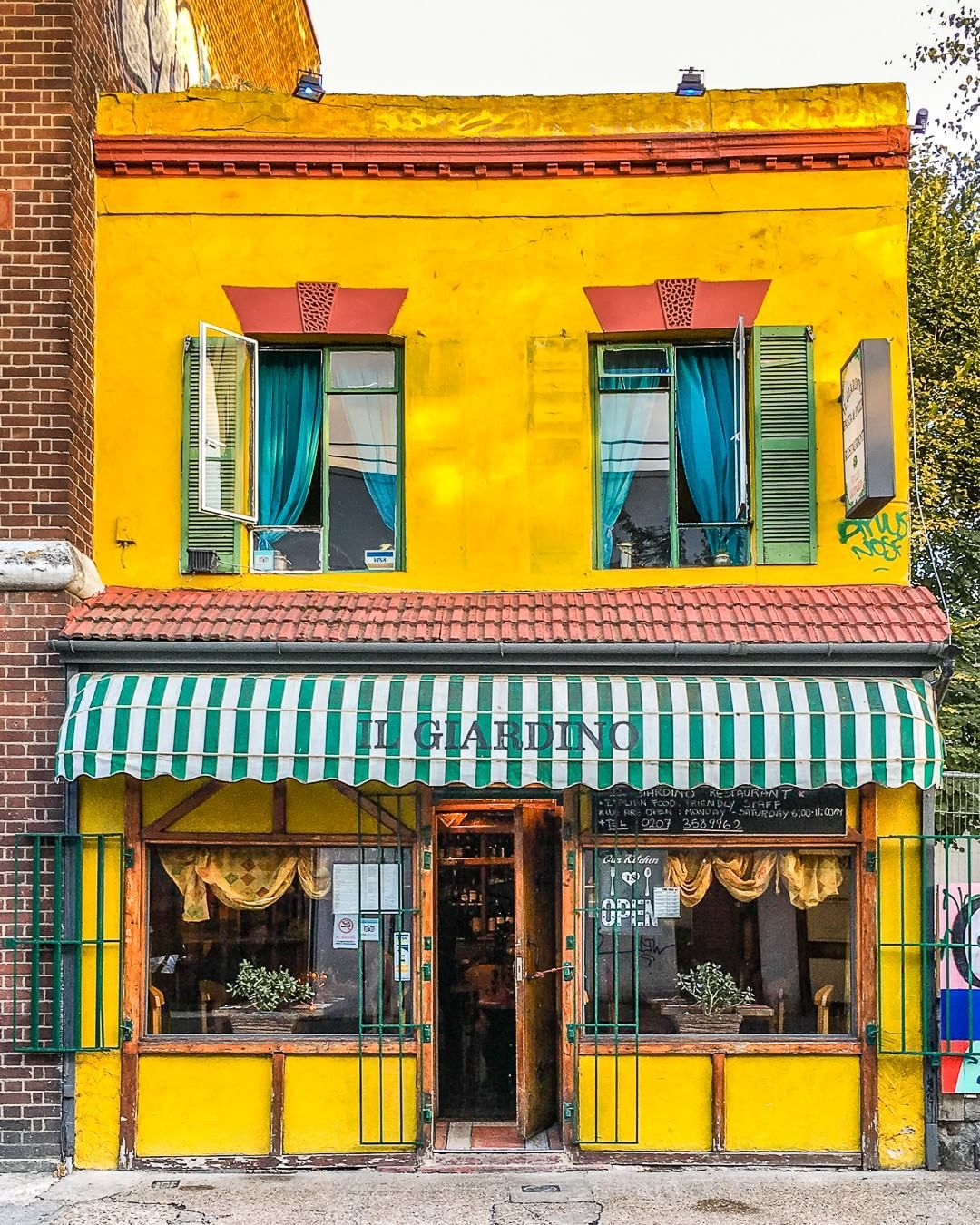 A Bright Yellow Facade On A Restaurant In London S Peckham The Green And White Striped Awning Adds A Beautiful Design Touch Restaurant Peckham London Colo