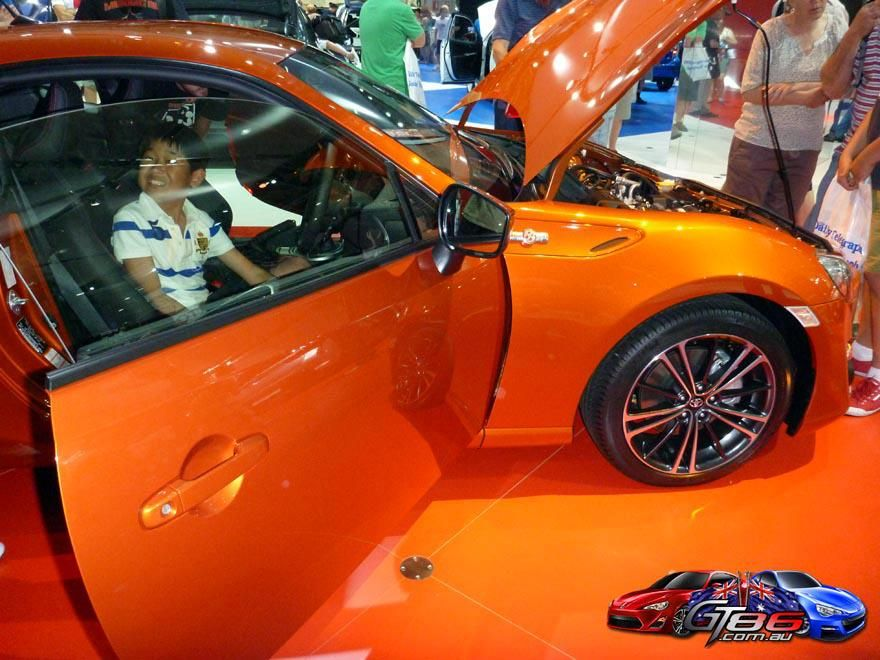 A little kid just loves this orange toyota 86 at the