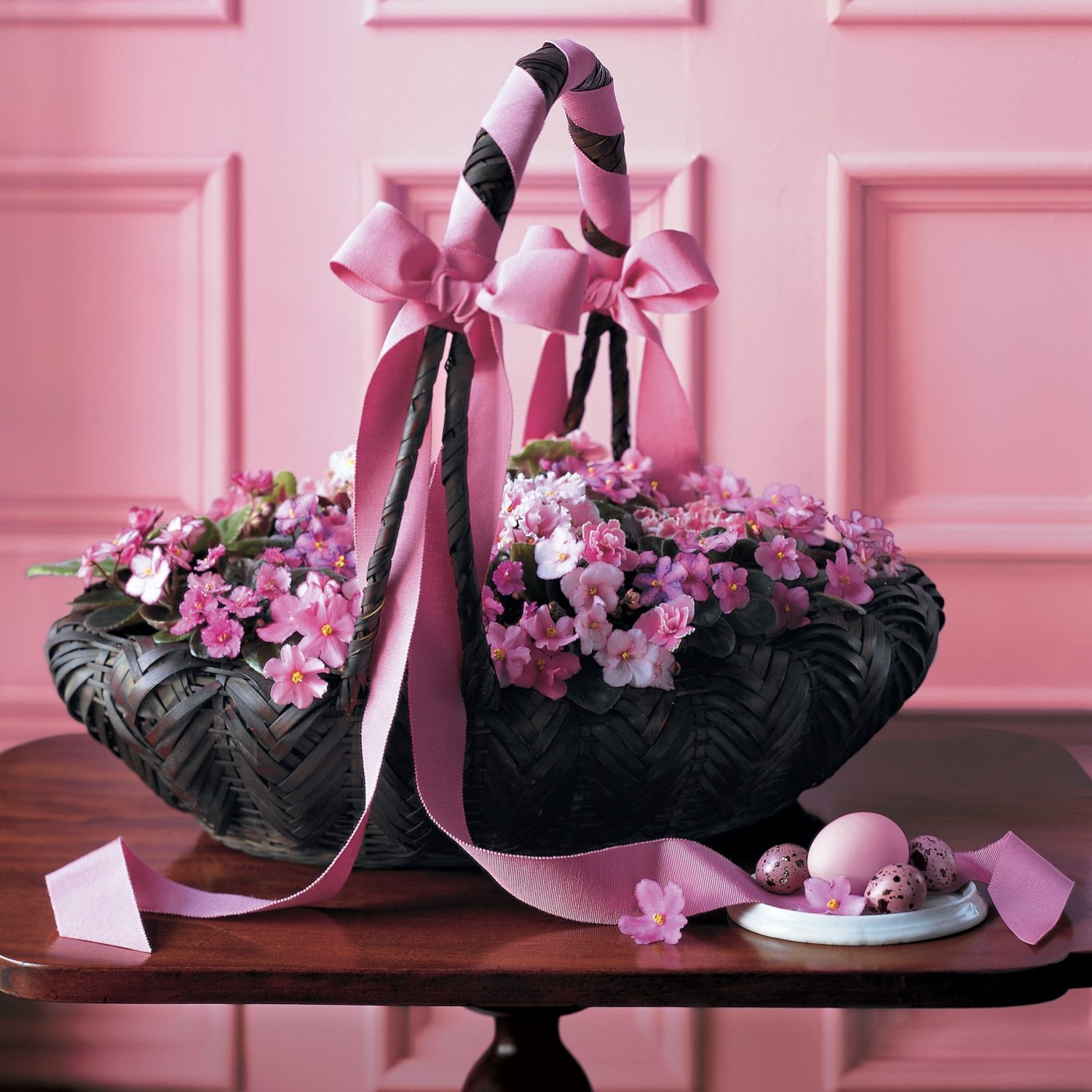 African violets shine amongst pink Easter eggs in this Japanese oval basket.