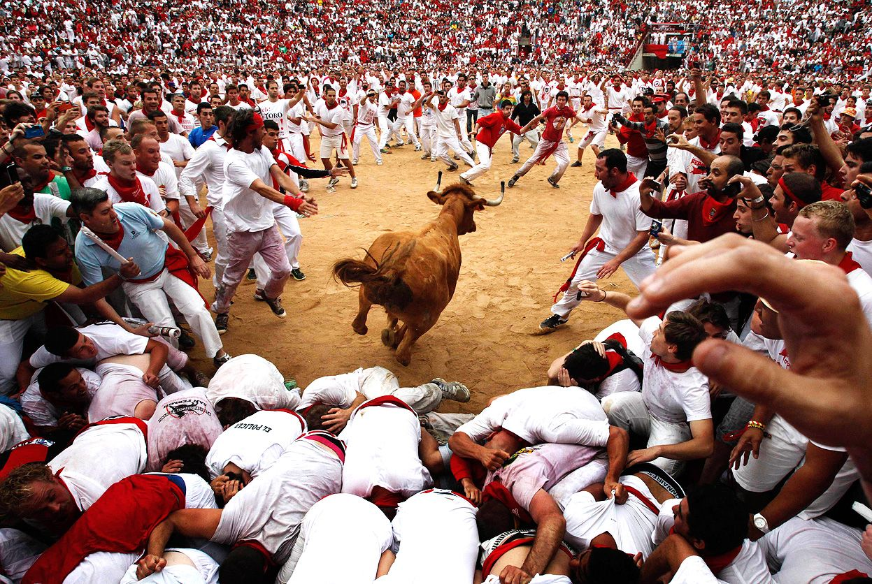 A cow jumps over revelers in a bullring during the second running of the bulls at the San Fermin Fiesta, in Pamplona, Spain, on July 8, 2012
