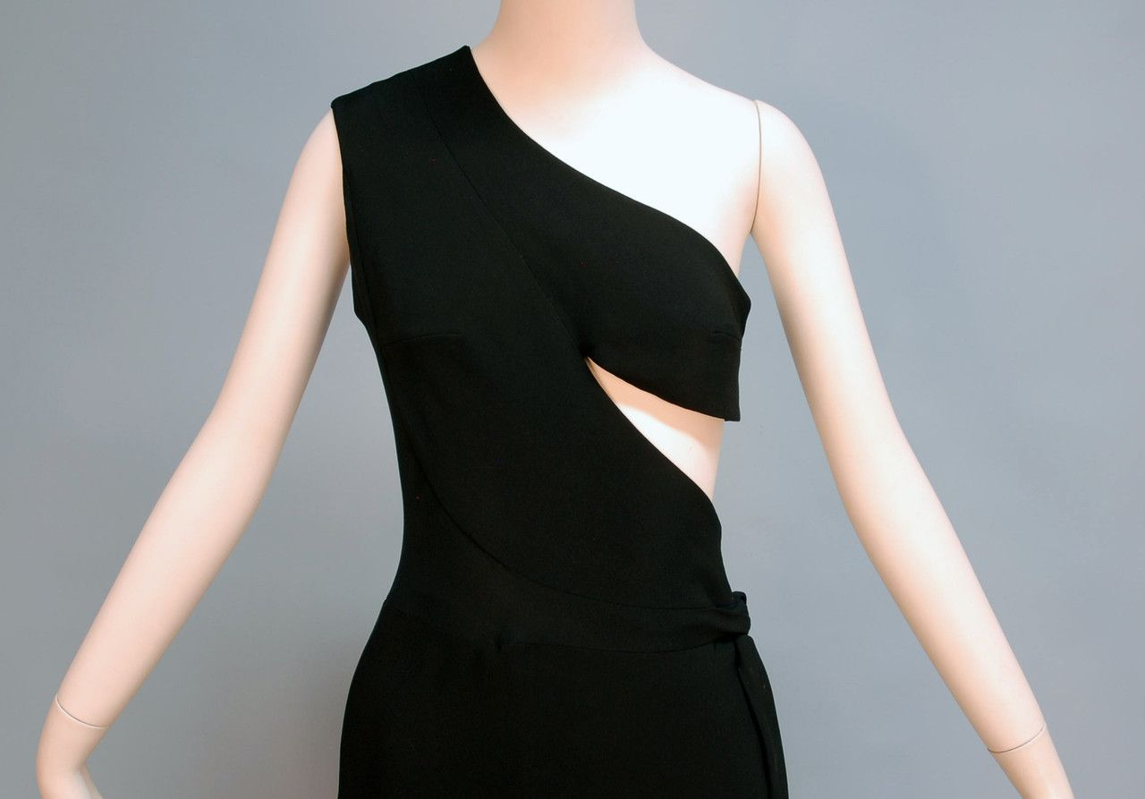 MADAME GRES ASYMMETRICAL ONE-SHOULDER GOWN, c. 1970. Black rayon faille wrap style with triangular side cutout, side self tie over hook and eye closures and snaps, Paris label. Detail