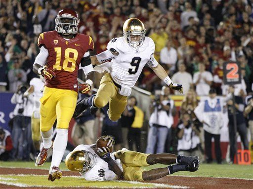 Notre Dame wide receiver Robby Toma, top, jumps onto running back Theo Riddick, bottom, to celebrate after Riddick dove into the end zone for a touchdown vs USC