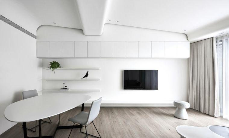 Soggiorno minimal con mobili sospesi di colore bianco e tv appesa