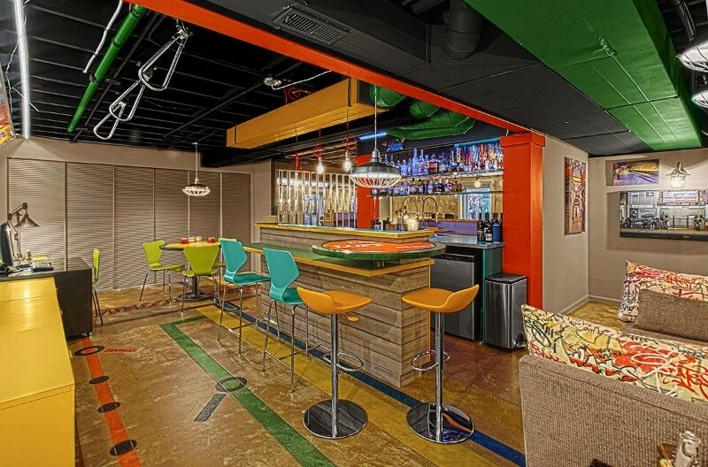 Eclectic Basement Mancave With Exposed Ceiling, Brightly Colored Bar  Stools, Fully Stocked Bar And
