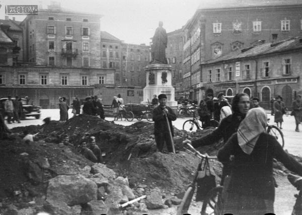 In einem Bombenkrater am Mozartplatz in Salzburg werden die Leitungen repariert. Im Hintergrund ist das Café Glockenspiel zu sehen.