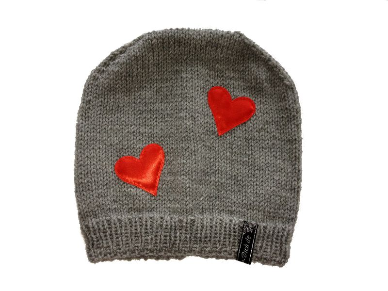 Hier biete ich eine super schöne gestrickte Mütze in grau mit aufgenähten Herzen an.     Ein echter Hingucker.