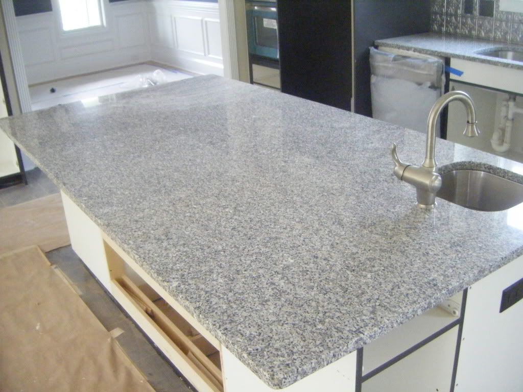 Black And Gold Granite Counters With White Cabinets