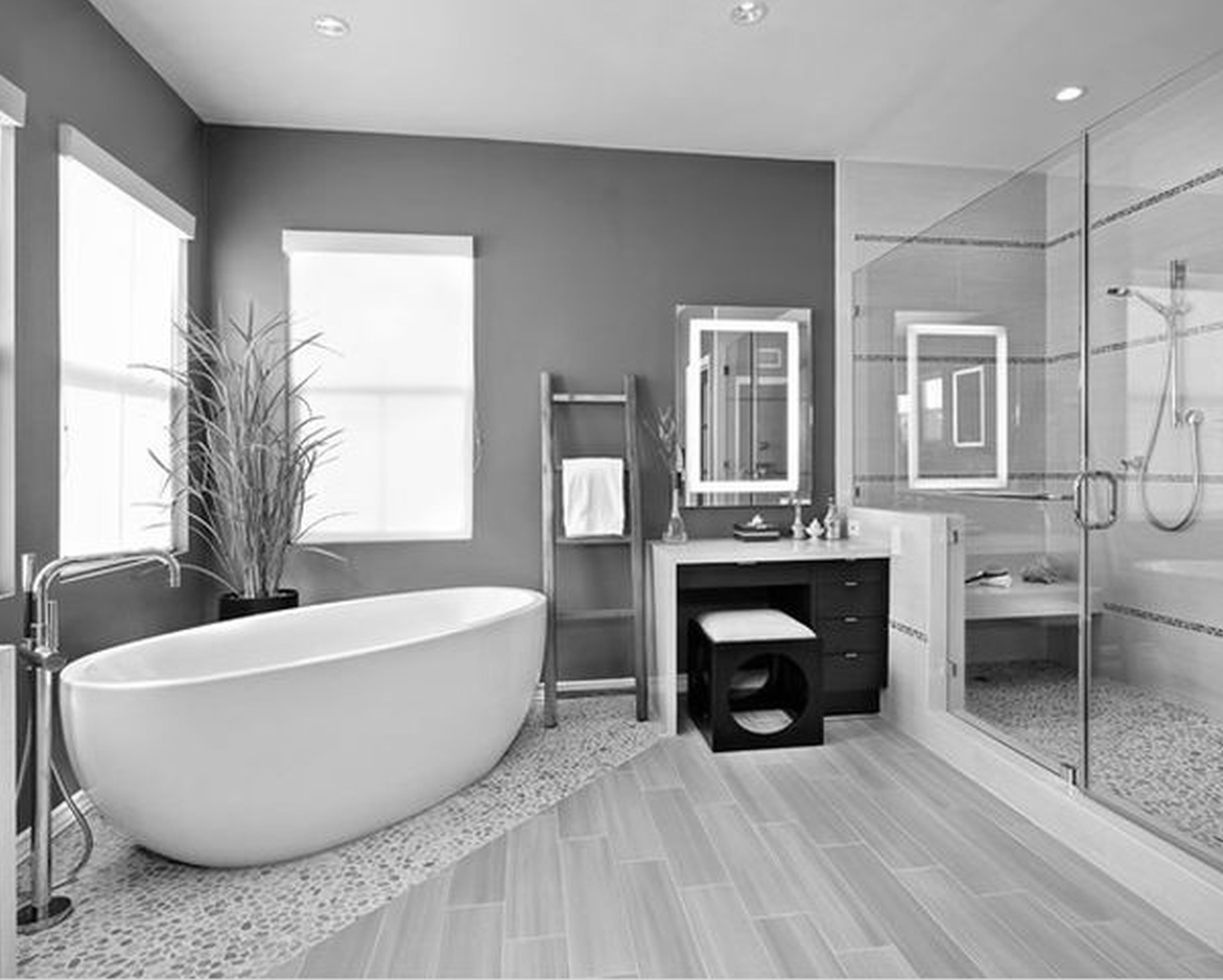 charming white porcelain soaking tub on black floor tiles for