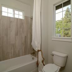 coastal guest bathroom with wood-look tile shower   shower