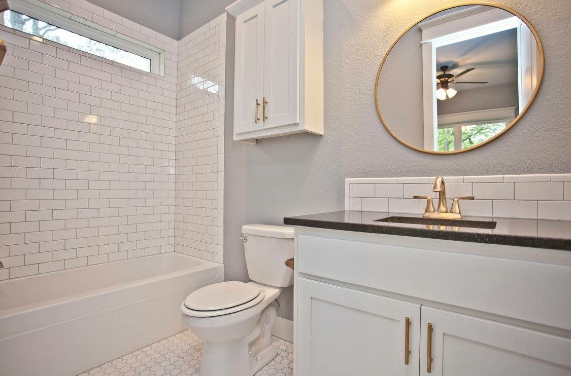 Guest bathroom with white subway tile backsplash black pearl guest bathroom with white subway tile backsplash black pearl granite countertops satin brass round mirror light fixtures and cabinet pulls dailygadgetfo Image collections