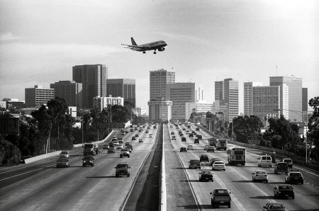 A view of an airliner flying over Interstate 5 as it makes its approach to Lindbergh Field. The downtown San Diego city skyline can be seen in the distance.