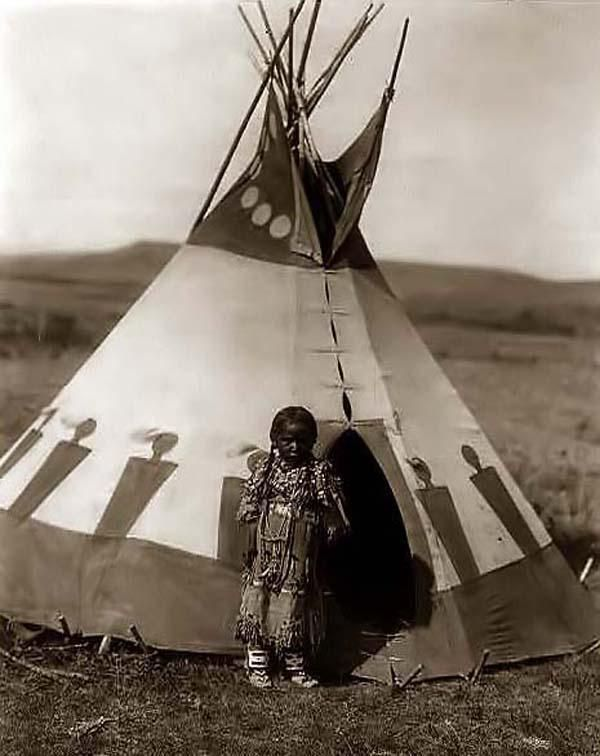 Piegan girl standing outside small tipi.1910 Edward S. Curtis