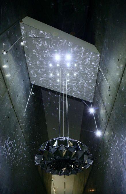 1枚の布にステンレスミラーを貼り合わせて折ったものを伸縮させることで、多様な光の反射を見せる