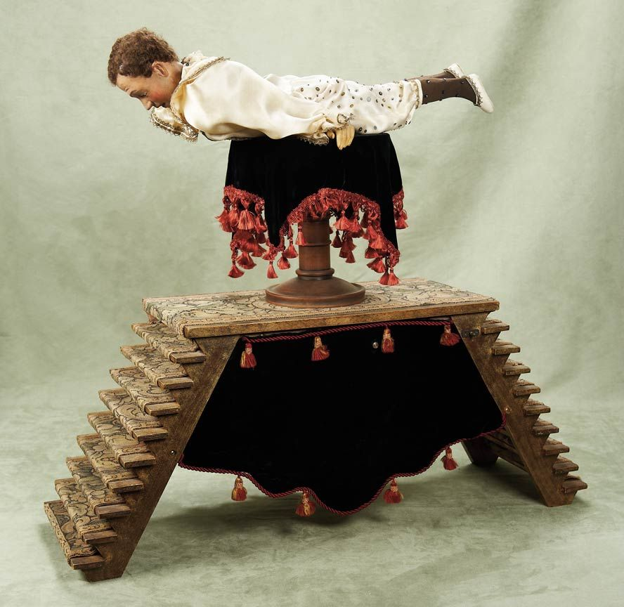 """An Outstanding French Musical Automaton """"L'Homme Serpent"""" of Vichy Lineage 34"""" (86 cm.) l. base,24"""" acrobat,39"""" overall h. A wooden pedestal table with velvet cover is set center-stage on a tapestry-covered platform with nine-steps on either side. Posed upon the platform is an acrobatic contortionist, completed in the late 20th century"""