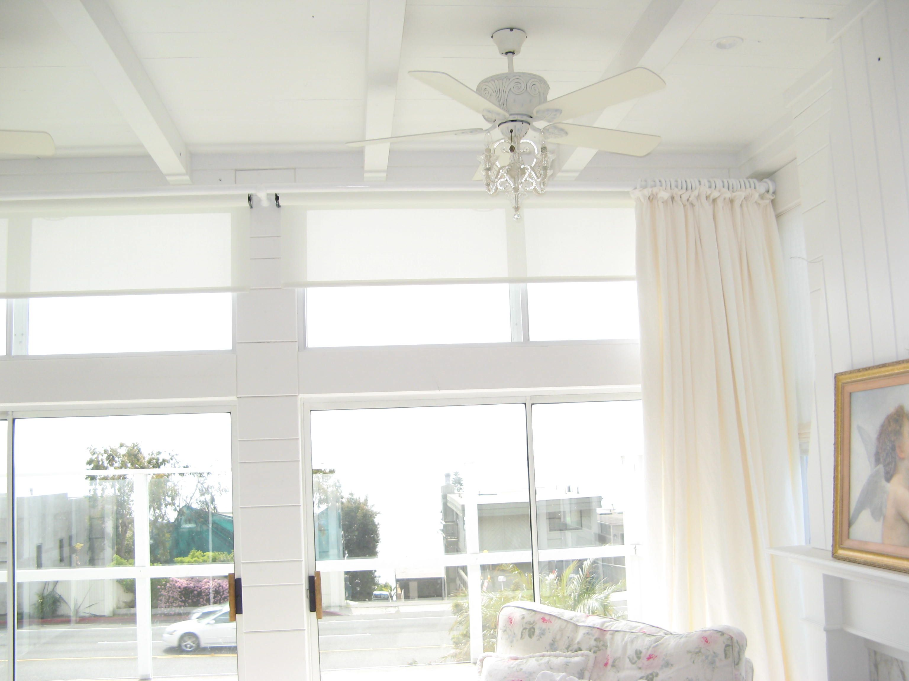 Soft, Warm and Casual. Motorized Solar Shades with Shabby Heading Stationary Drapes on White wood pole.