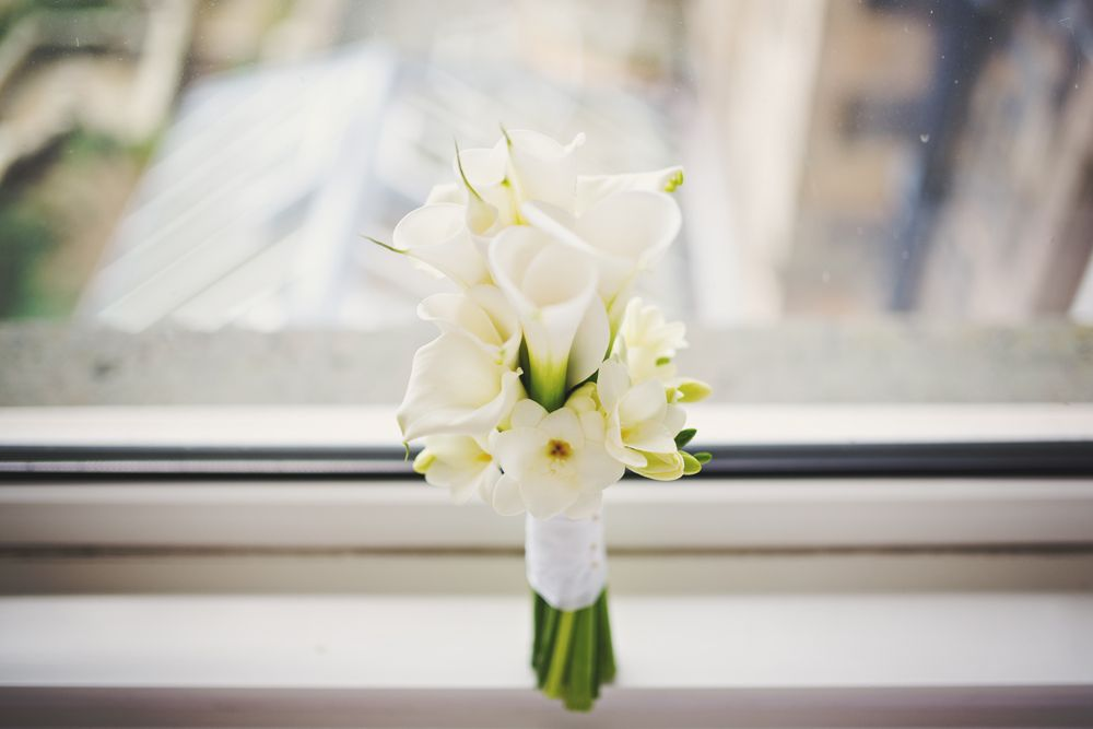 Calla lily bridal bouquet with a collar of freesia.