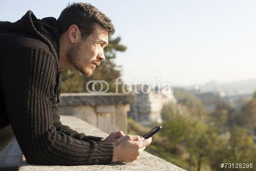 """Laden Sie das lizenzfreie Foto """"Attractive Man Holding The Mobile Phone Outdoor"""" von hitmanphoto zum günstigen Preis auf Fotolia.com herunter. Stöbern Sie in unserer Bilddatenbank und finden Sie schnell das perfekte Stockfoto für Ihr Marketing-Projekt!"""