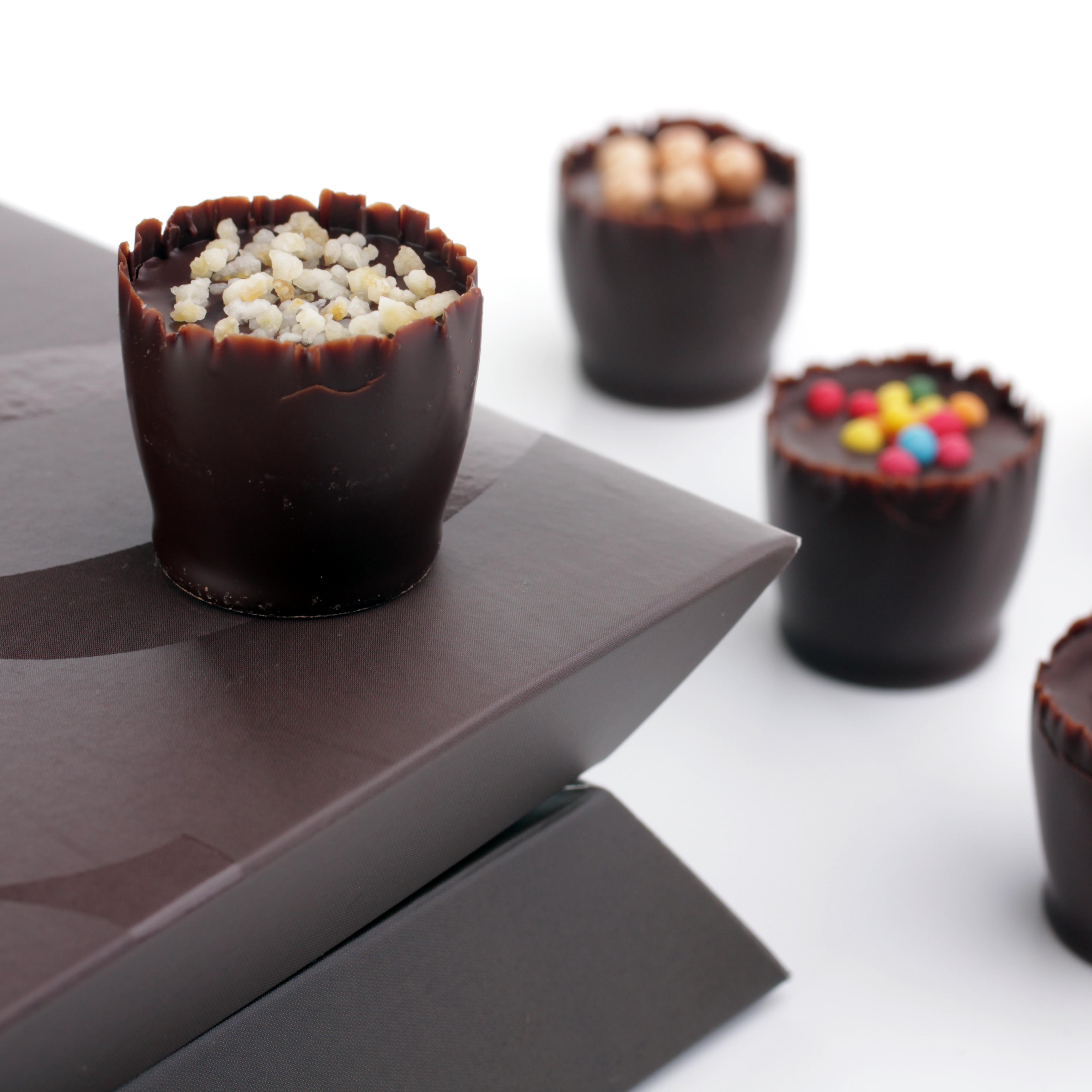 A csokoládé formáját és csomagolását 2013-ban terveztük. Feladatunk az volt, hogy - a kijelölt célközönség ízlésének megfelelően - szokatlan, mégis praktikus formába öntsük a különleges, kézzel készült édességeket. A termékpaletta folyamatosan bővül és a bonbonok már egész Európában kaphatók. A csomagolás 2014-ben Pro Typo díjat, 2015-ben pedig Magyar Termék Nagydíjat nyert.