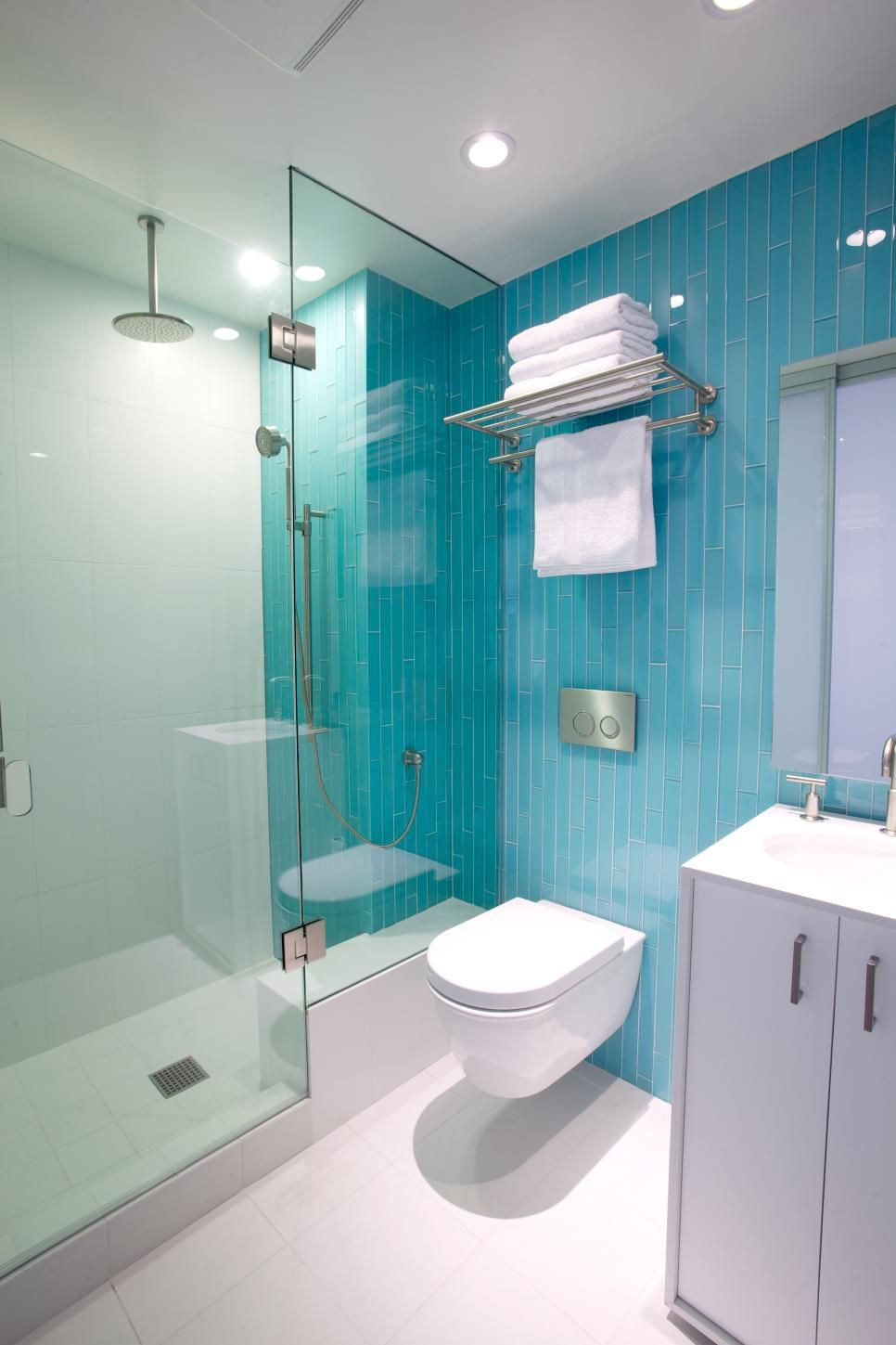 This bold master bathroom features vertical rectangular turquoise ...
