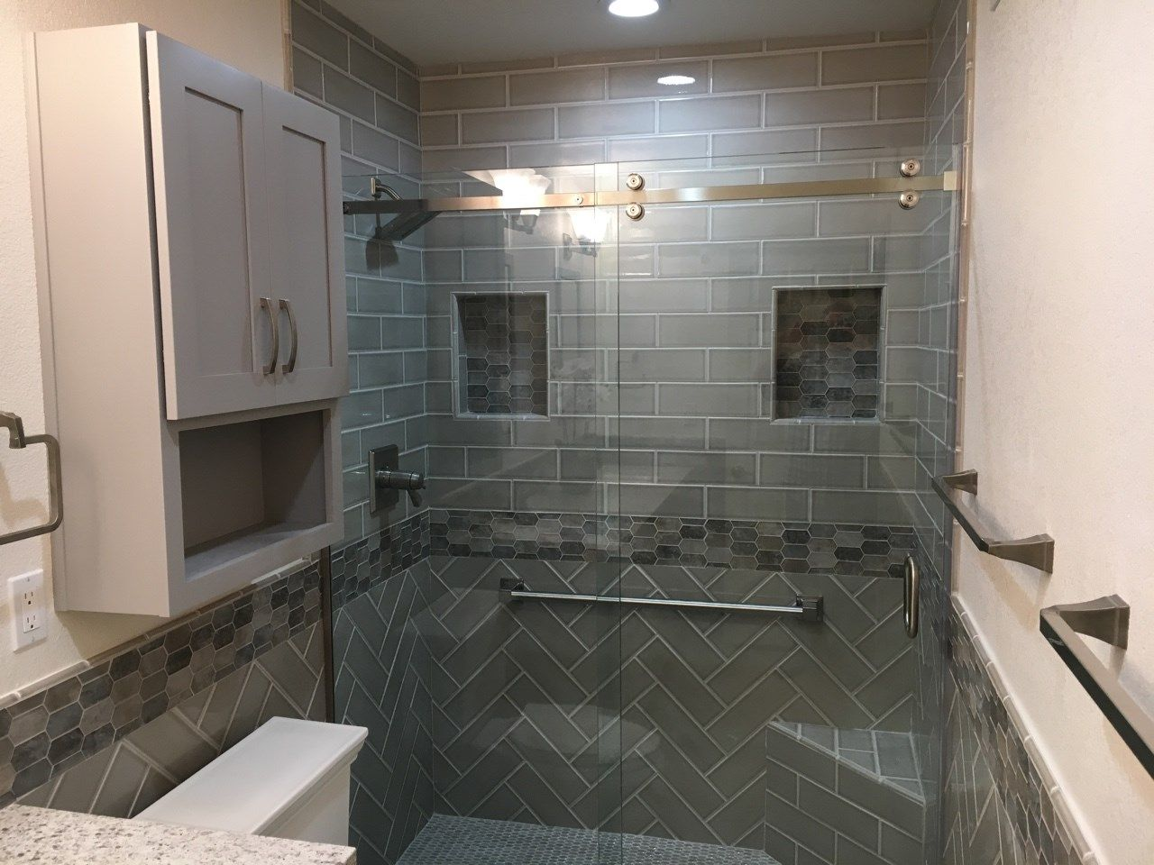A Mix Of Brick Lay Tile And Herringbone Lay 4 X 12 Tile Separated By A Charismatic Glass Mosaic B Home Remodeling Contractors Bathroom Design Dream Bathrooms