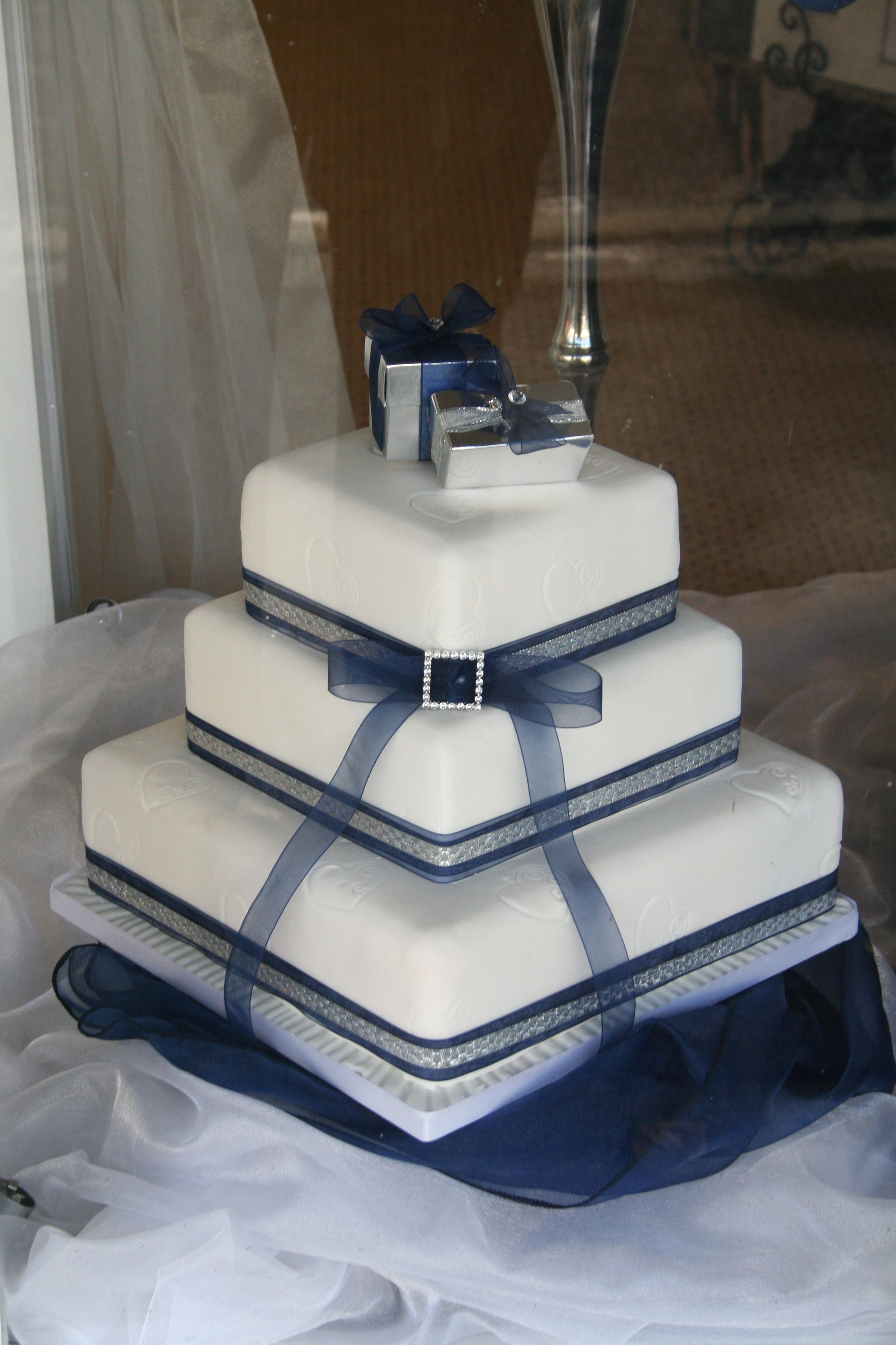 White Wedding Cake Decorated With Midnight Blue Silver Ribbon Boxes Available From