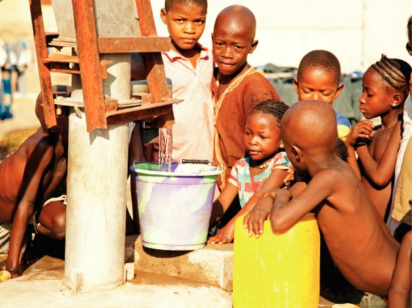 A group of African children standing by a water pump and watching water flow into a bucket.