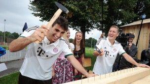 1. September, #Bayern: Javier Martinez (l.) und Bastian Schweinsteiger vom Fußball-Bundesligisten FC Bayern München tragen in München das neue Auswärtstrikot des Rekordmeisters und schlagen mit einem Hammer Nägel ins Nagelbrett. Foto: dpa