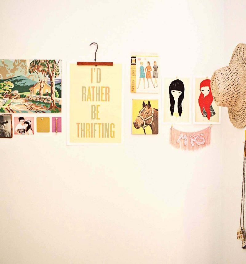 love this way of using a vintage coat hanger to display wall art ...