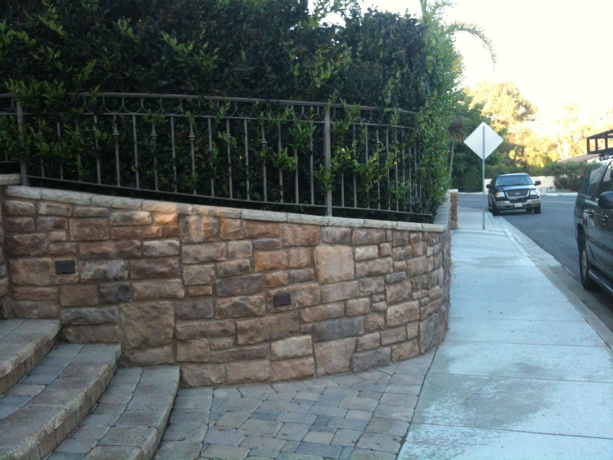 Curved stairs stone work on retaining wall fence on wall for Curved garden wall ideas