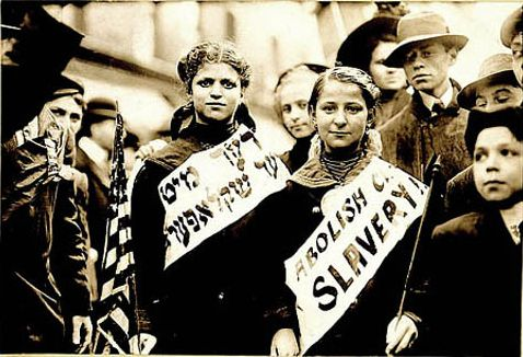 "These women, marching on May 1, 1909 in New York, wear signs reading ""Abolish Child Slavery"" in English and Yiddish. Jewish workers in the US began forming unions [pdf] in the 1880s, and the Jewish labor movement experienced a turning point in the 1930s as Jewish workers turned away from Communism and began to respond to growing anti-Semitism worldwide."