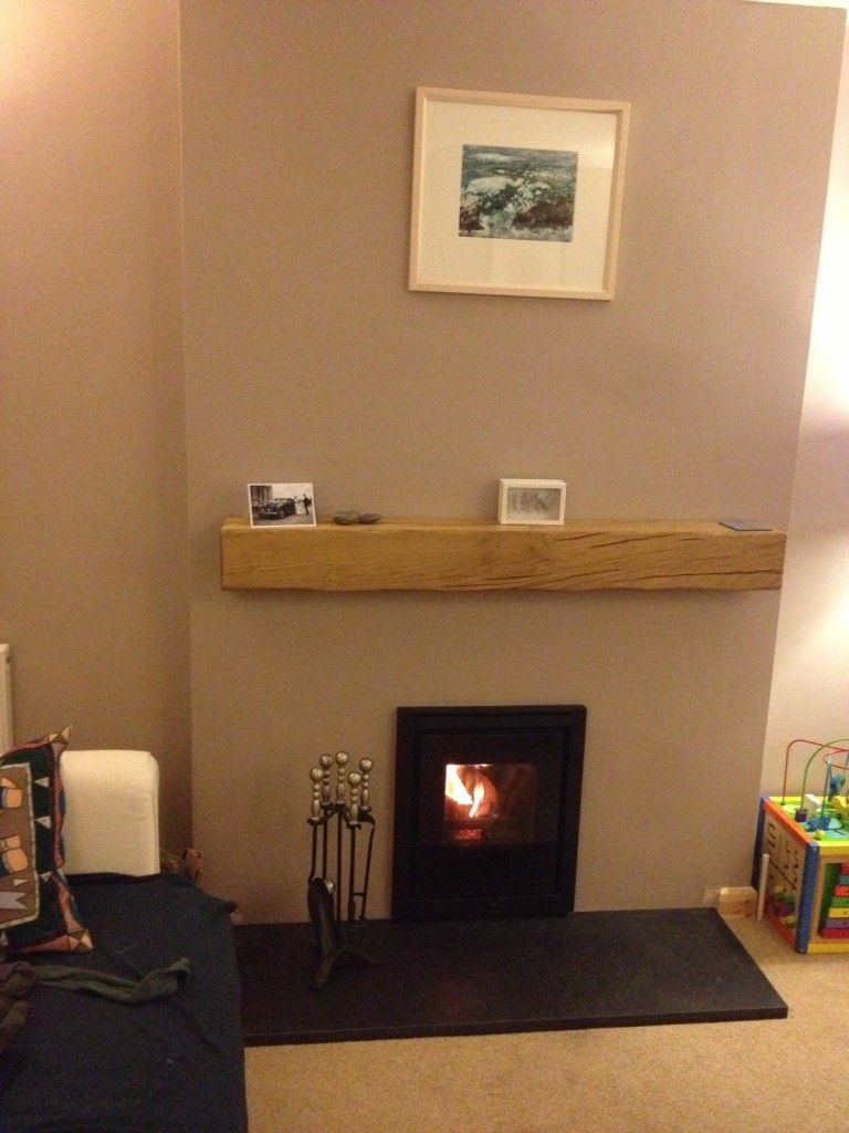 inset wood burning stove installed with floating oak beam and