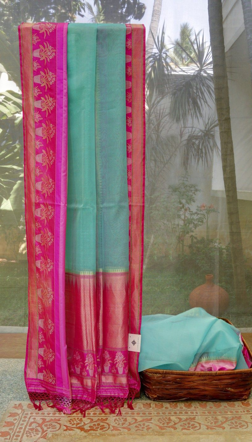 This striking sky blue sari is a light benares kora. The border has bands of magenta,hot pink, fuchsia pink and rose pink with flower pots delicately woven in gold zari and silver zari into a lovel…