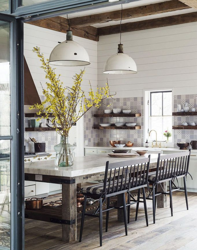 An Eclectic Farmhouse Kitchen Boasts Tiled Walls Industrial Pendants And Counter Bench Seats