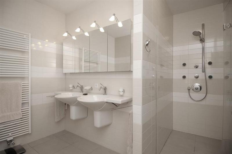 De badkamer heeft een dubbele wastafel, een regendouche en een ...