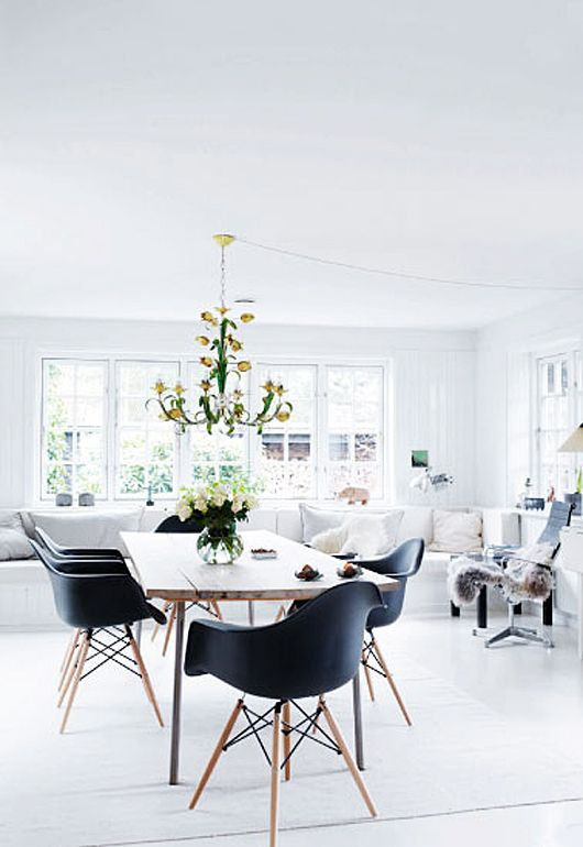 Stunning simplicity of all black and white with a pop of color from a flea-market found chandelier inside a black-shingled cabin in Demark