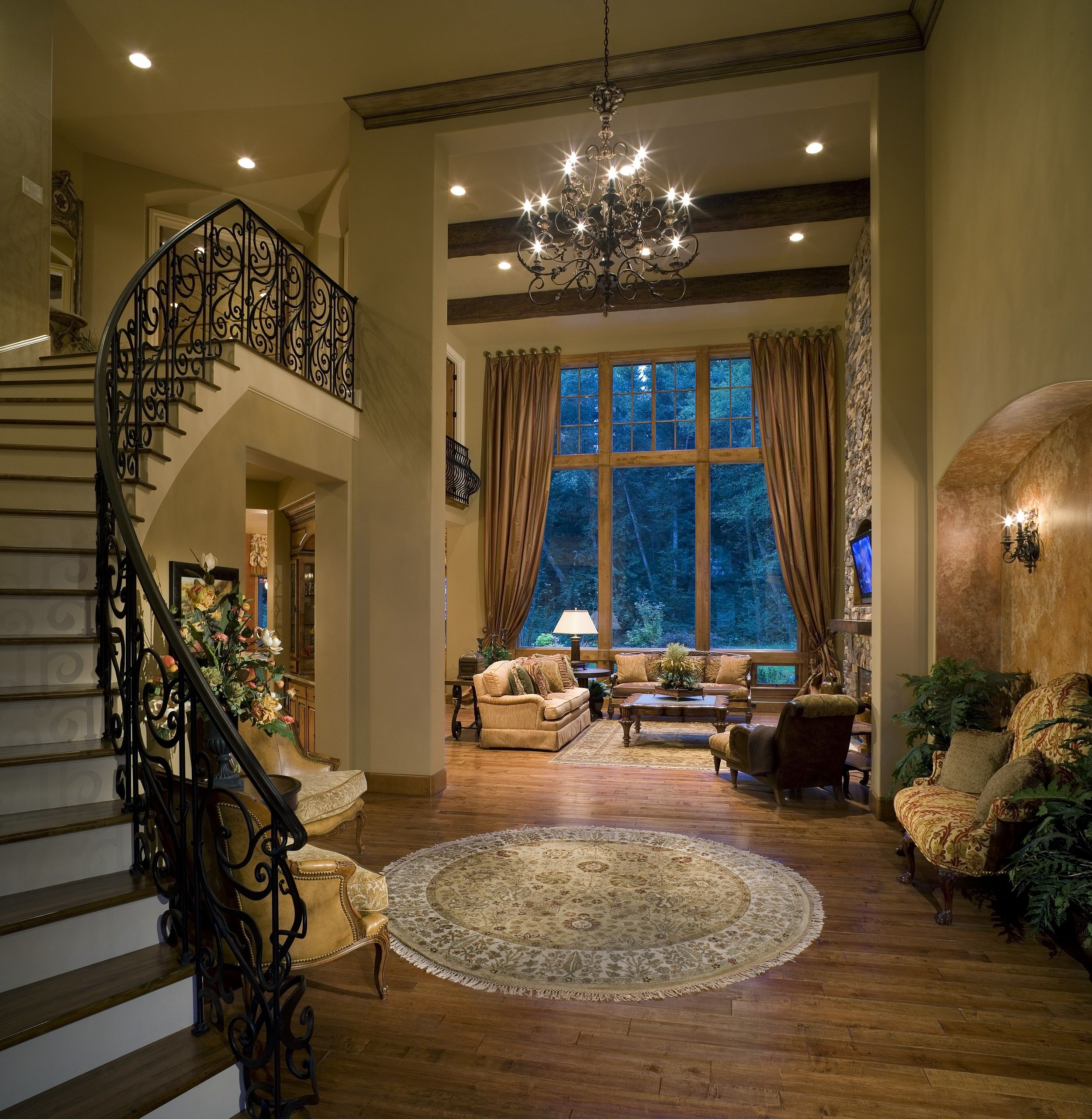 This entrance screams, come into our home! a gorgeous home with hardwood floors, an elegant staircase and a charming chandelier. Click to see how much it costs to install a light fixture.
