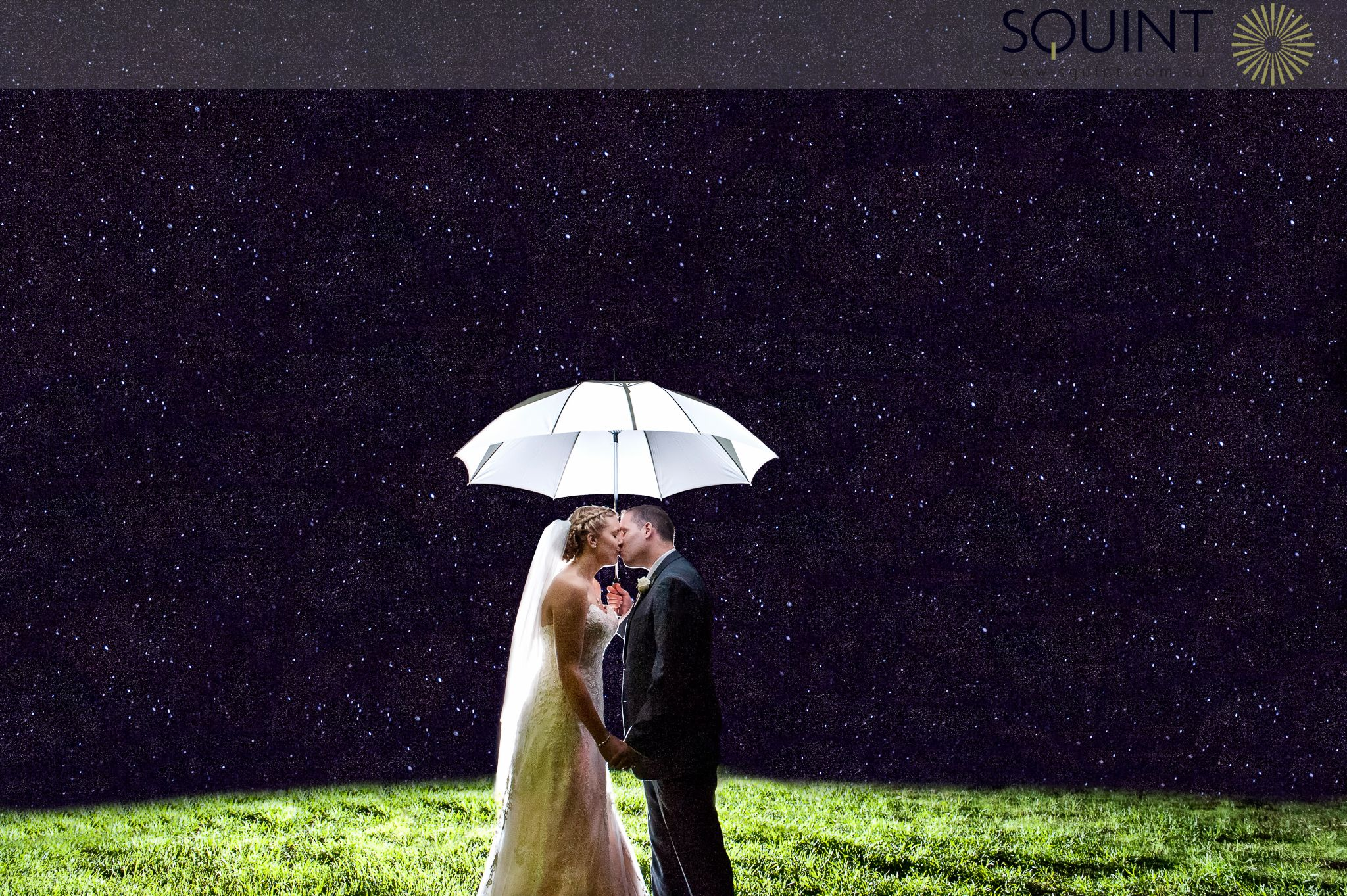 Spectacular bride and groom under umbrella in the rain at night