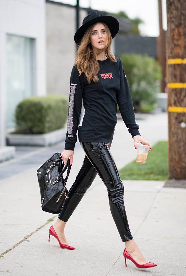 bd8571fd9 Chiara Ferragni com look hi-low de maxi moletom preto, calça de verniz  preta e scarpins de verniz vermelhos, arrematando com chapéu e bolsa  Balenciaga