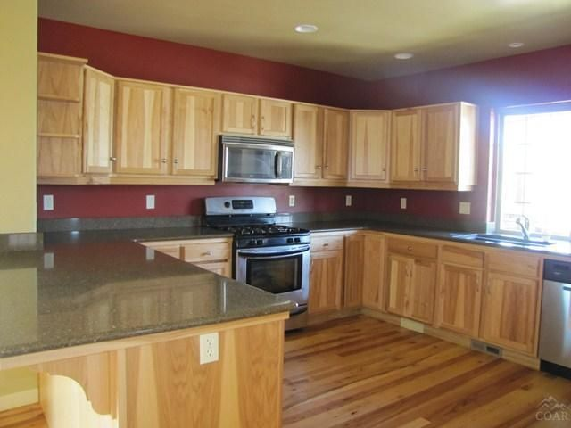 Love! Hickory Cabinets with deep red painted walls. I'd ...