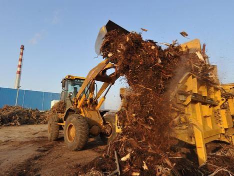 Työntekijä siirtää haketta Kaidin biomassatehtaalla Kiinassa Anhuin maakunnassa.