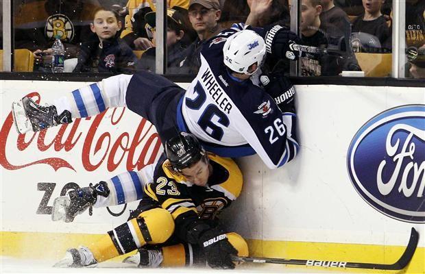 Chris Kelly 23 Of The Boston Bruins Checks Blake Wheeler 26 Of The Winnipeg Jets On January 10